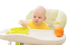 Bebê que senta-se comendo o alimento de colher a casa da tabela Imagem de Stock