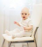 Bebê que senta-se na cadeira em casa e nos olhares na câmera Foto de Stock Royalty Free