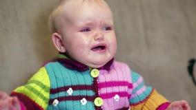 Bebê que senta-se na casa e que grita, embreando sua cabeça vídeos de arquivo