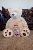 Bebê que senta-se na frente do urso de peluche gigante Fotos de Stock