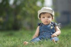 Bebê que senta-se na grama Imagens de Stock Royalty Free