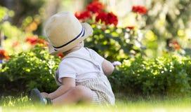 Bebê que senta-se na grama no jardim no dia de mola bonito fotografia de stock