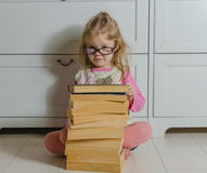 Bebê que senta-se no assoalho com a pilha de livros com vidros foto de stock royalty free