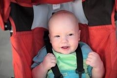 Bebê que senta-se no carrinho de criança imagem de stock