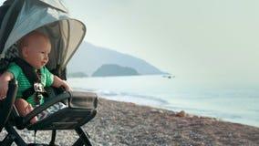 Bebê que senta-se no carrinho de criança na praia Bebê recém-nascido no carrinho de criança que olha o mar filme
