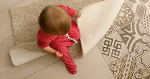 Bebê que senta-se no tapete video estoque