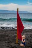 Bebê que senta-se perto da bandeira vermelha na praia vulcânica da areia do preto da arena do la de Playa Imagens de Stock Royalty Free