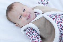 Bebê que sorri na cobertura branca Imagem de Stock
