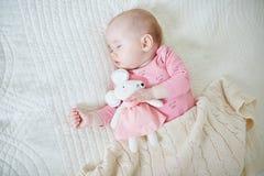Bebê que tem uma sesta com brinquedo do rato fotografia de stock royalty free