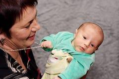 Bebê que tenta roubar a colar das avó Fotos de Stock Royalty Free