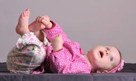 Bebê que toca em seu pé Imagens de Stock