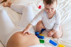 Bebê que toca na barriga à mãe grávida fotografia de stock royalty free