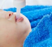 Bebê que toma a medicina com conta-gotas fotos de stock