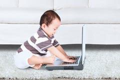 Bebê que usa um caderno Imagem de Stock
