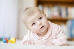 Bebê recém-nascido adorável que encontra-se na barriga no quarto ou no berçário ensolarado branco Imagem de Stock
