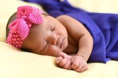 Bebê recém-nascido asiático no fundo amarelo envolvido com pano azul imagens de stock