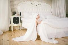 Bebê recém-nascido bebê idoso de cinco meses no quarto ao lado de uma grande cama branca no assoalho de madeira envolvido em uma  Foto de Stock Royalty Free