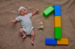 Bebê recém-nascido bonito que encontra-se com brinquedos - aniversário, celebração e contando o conceito Fotografia de Stock Royalty Free