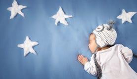 Bebê recém-nascido bonito que encontra-se na cama Criança do bebê de dois meses no chapéu da coruja que dorme na cobertura azul Fotos de Stock Royalty Free