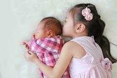 Bebê recém-nascido de sono de abraço da irmã asiática bonito que encontra-se no fundo branco da pele imagens de stock