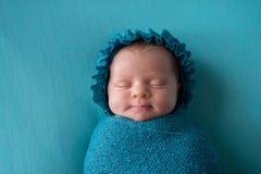 Bebê recém-nascido de sorriso que veste uma capota do azul de turquesa imagem de stock royalty free