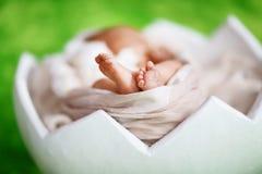 Bebê recém-nascido do close-up com os dedos minúsculos dos pés pequenos bonitos da em um lenço bege macio, em um shell do conceit fotografia de stock
