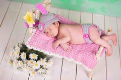 Bebê recém-nascido em um traje feito malha da lebre que dorme em um vidoeiro de madeira da ucha imagens de stock