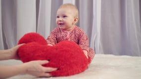 Bebê recém-nascido feliz que sorri e que joga com coração filme
