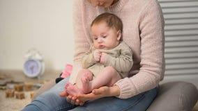Bebê recém-nascido minúsculo bonito que senta-se com os pés descalços no regaço da jovem senhora, cuidados com a pele da criança video estoque