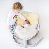 Bebê recém-nascido minúsculo no balanço com sua irmã da criança imagem de stock royalty free