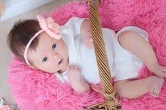 Bebê recém-nascido na cobertura cor-de-rosa que encontra-se na cesta que olha a câmera com opinião superior do interesse Filha in Foto de Stock