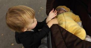 Bebê recém-nascido que coloca na ucha seus irmãos que olham o vídeos de arquivo