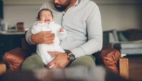 Bebê recém-nascido que grita em seu regaço do ` s do pai Foto de Stock Royalty Free