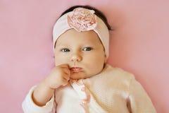 Bebê sério que olha a câmera que encontra-se no fundo cor-de-rosa Retrato de um pouco bonito Fotografia de Stock Royalty Free