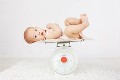 Bebê sobre na escala de peso Fotografia de Stock