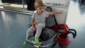 Bebê triste que senta-se em sacos na sala de espera vídeos de arquivo