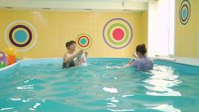 Bebês bonitos que treinam com instrutores nadadores vídeos de arquivo