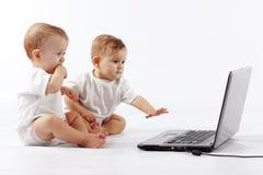 Bebês com portátil Foto de Stock Royalty Free