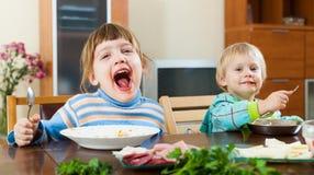 Bebês emocionais felizes que comem o alimento na tabela Imagem de Stock