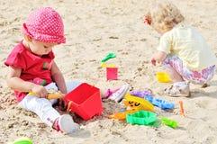 Bebês que jogam brinquedos na areia Foto de Stock Royalty Free