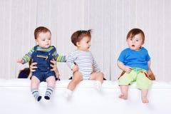 Bebês que sentam-se no sofá para trás foto de stock royalty free