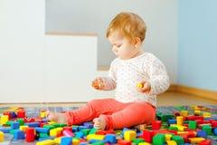 Beb? ador?vel que joga com brinquedos educacionais Crian?a saud?vel feliz que tem o divertimento com blocos de madeira diferentes imagem de stock
