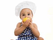 Bebé adorable con el casquillo del cocinero que come la pera Imagen de archivo libre de regalías