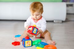 Beb? adorable que juega con los juguetes educativos en cuarto de ni?os Ni?o sano feliz que se divierte con diversos juguetes colo fotografía de archivo