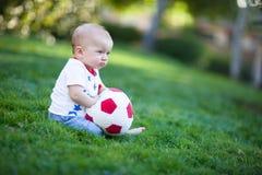 Bebé adorable que sostiene un balón de fútbol rojo y blanco Imagenes de archivo
