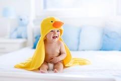 Bebê bonito após o banho na toalha amarela do pato Foto de Stock