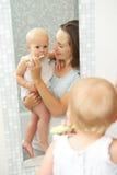 A bebê bonito feliz da mãe ensinando como escovar os dentes Imagem de Stock Royalty Free