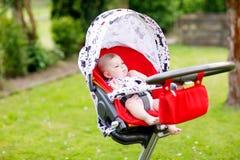 Beb? bonito pequeno bonito de 6 meses que sentam-se na mam? do pram ou do carrinho de crian?a e da espera foto de stock