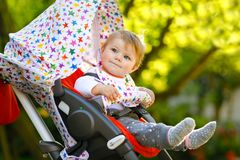 Beb? bonito pequeno saud?vel bonito que senta-se na mam? do pram ou do carrinho de crian?a e da espera Crian?a de sorriso feliz c foto de stock