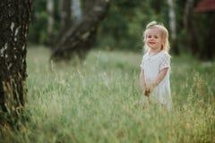 Beb? bonito que anda em um jardim ensolarado com uma cesta menina em um vestido branco com uma cesta no parque foto de stock royalty free